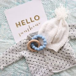 Blue teether toy on a baby cardigan with hat and a card that says Hello Sunshine