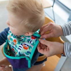 Baby wearing a colourful bib with a fold up pocket