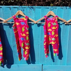 Row of red dino dungaress against a blue fence
